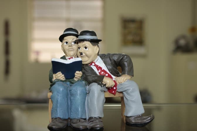 Two men reading a book