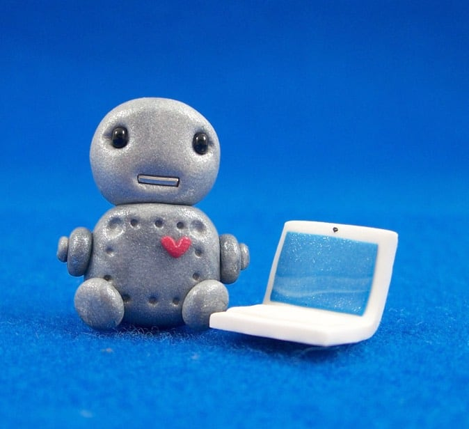 A little robot next to a computer